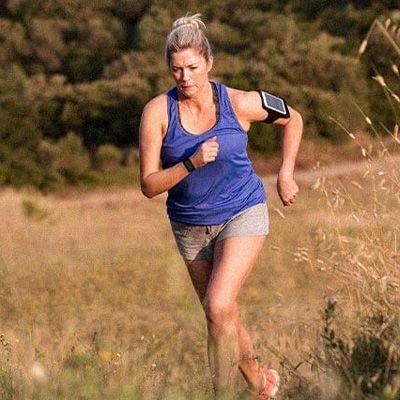 dame som jogger utendørs med pulsklokke